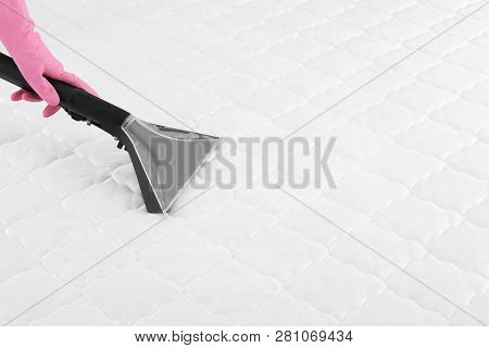 Person Disinfecting Mattress With Vacuum Cleaner, Closeup. Space For Text