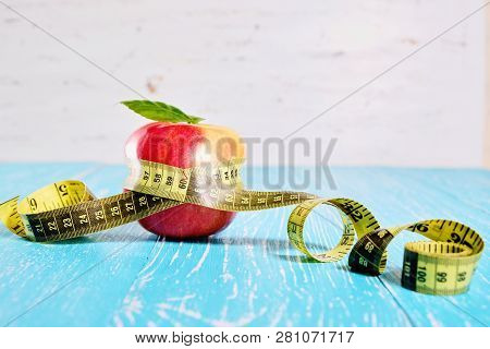 Measuring Tape Around An Apple. Diet And Weight Loss Concept
