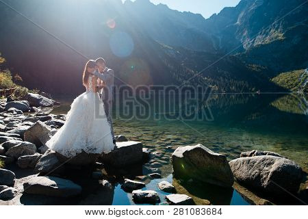 Romantic Groom And Bride In Beautiful White Wedding Dress Standing On The Stony Shore Of The Morskie