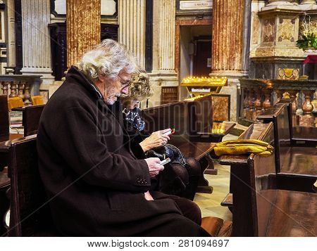 Turin, Italy - December 30, 2018. A Couple Of Senior Tourists Consulting Information In His Mobile P