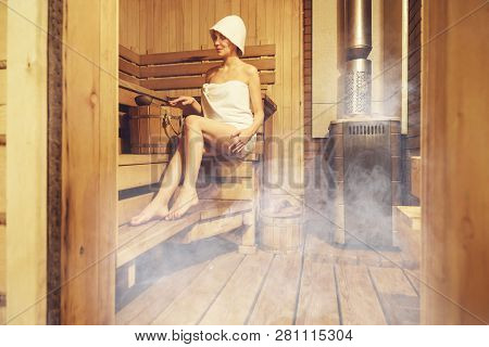 Young Beautiful Woman Relaxing In The Finnish Sauna Wrapped In Towel. Interior Of Finnish Sauna, Cla