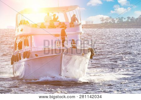 Boat With People Silhouette On On Ocean Water At Sunrise With Flare And Outdoor Lifestyle