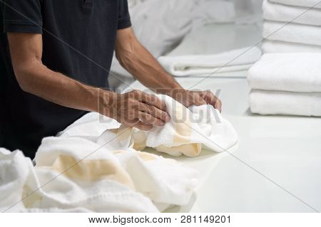 Hands Of Caucasian Male Laundry Hotel Worker Folds A Clean White Towel. Hotel Staff Workers. Hotel L