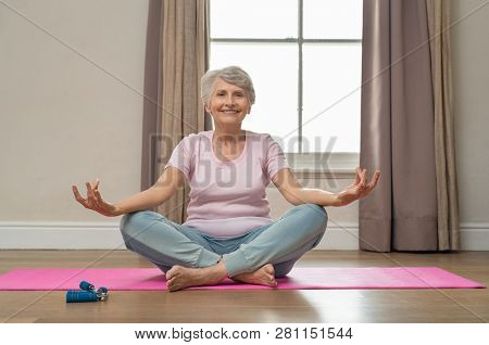 Senior smiling woman doing yoga in her living room. Elderly relaxed woman sitting in lotus pose and meditating while practicing yoga at home. Old grandmother sitting on yoga mat smiling.