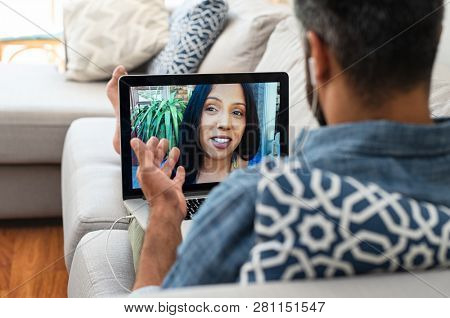 Closeup of woman talking through video chat on laptop with her boyfriend. Mature man communicating with his mixed race girlfriend on laptop in video chat. Man and woman talking to each other.