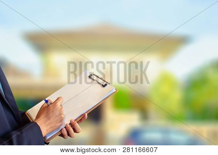 Man Business Salesman Sell House With Computer On House And Tree Blurry Background.for Home Business