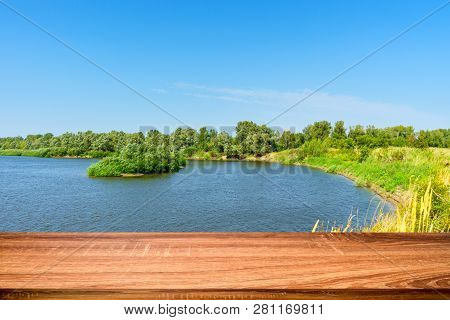 Empty wooden table with summer background of riverside in the daytime. Can be used for display or montage products poster