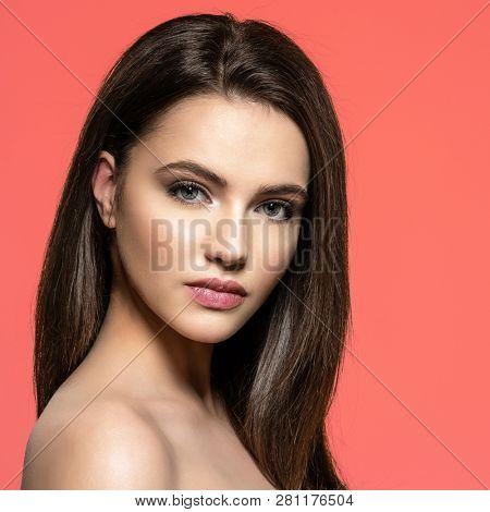 Woman with beauty long brown hair. Fashion model with long straight hair. Fashion model posing at studio.Pretty woman with long straight brown hair looking at camera. Pantone 2019.