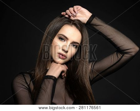 Woman with beauty long brown hair. Fashion model with long straight hair. Fashion model posing at studio.