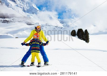 Family Skiing In Mountains. Mother And Kid Ski.