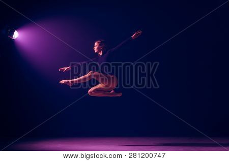 Young Female Ballet Dancer Dancing On Neon Lights Studio Background. Ballerina Project With Caucasia