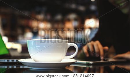 Closeup Coffee Cups Over The Photo Blurred Of Asian Woman Using The Smart Mobile Phone With Happines