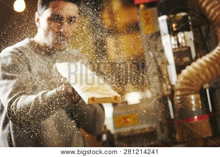 Man blows sawdust off the wood after sanding CNC router machine. Device with numerical control. poster