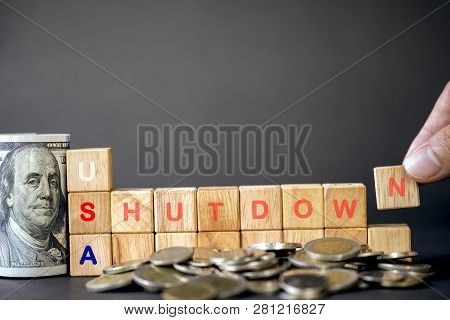 Human Hand Putting Usa Shutdown Wording On Wooden Cubes And Us Dollar Banknote And Coins On Black Ba