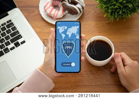 Female Hands Holding Phone With App Vpn On The Screen Above The Table In The Office