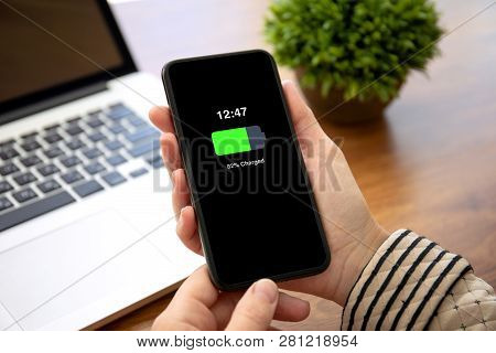 Female Hands Holding Phone With Charged Battery On The Screen Above The Table In The Office