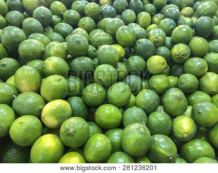 Lemons. Green lemons. Pail of green lemons. lemons ready for sale. Juice of green lemons is called lemoanda. Lots of fresh green lemons fruits plucked from branch of lemon tree.