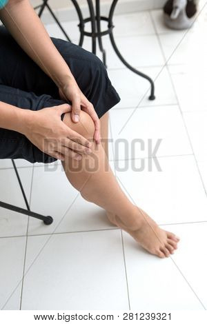 Woman holding right knee with her two hands indicating discomfort poster