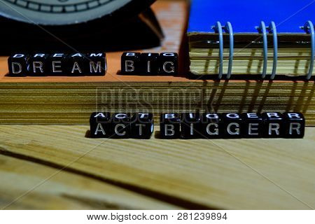 Dream Big Act Bigger Written On Wooden Blocks. Education And Business Concept On Wooden Background