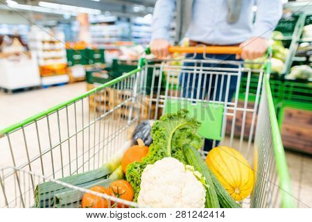 Man shopping in supermarket pushing his trolley with vegetables and groceries