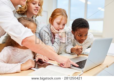 Teacher helps student team at work on laptop in computer lesson
