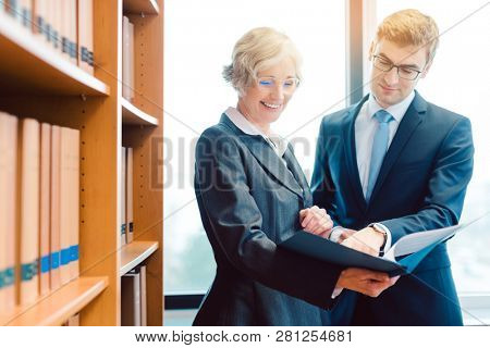 Senior and junior lawyer in law firm discussing strategy in a case reading the file