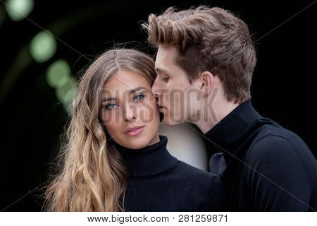 beautiful model fashion couple kissing wearing winter clothing,