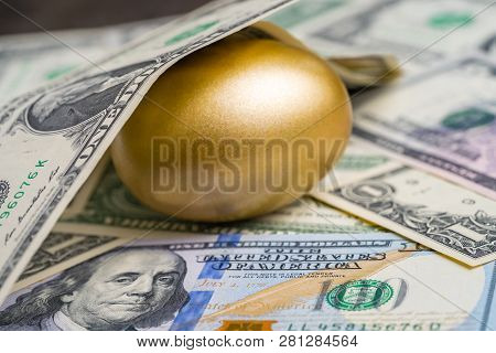Shiny Golden Egg Under Pile Of Us America Dollar Banknotes Money Metaphor Of Finding The Unbelievabl