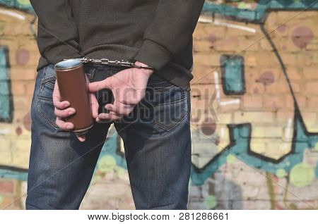 A Rear View Of An Arrested Street Artist In Handcuffs With Aeros