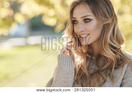 Fashion Autumn Portrait Woman With Yellow Maple Leaves On Nature Background. Pretty Woman Walking In