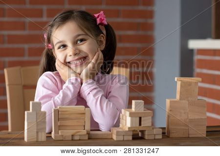 Happy Smiling Child Girl Playing With Wooden Toys At Home