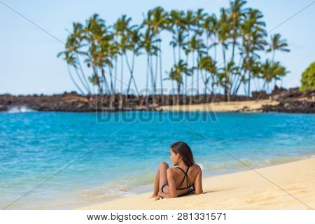 Hawaii beach summer vacation travel in Big Island, Hawaii, USA. Hawaiian secluded beach destination woman relaxing lying down on white sand at tropical holiday sun tanning. Skin care suntan concept.