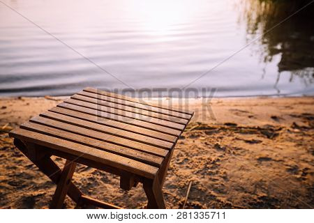 Small Wooden Stool Is Standing On The Beach By The Shore Of The Lake.