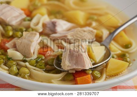 Portion of chicken noodle soup closeup