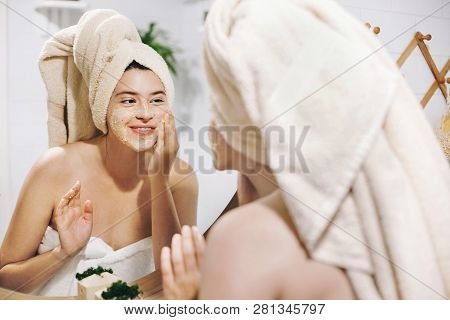 Skin Care Concept. Young Happy Woman In Towel Making Facial Massage With Organic Face Scrub And Look