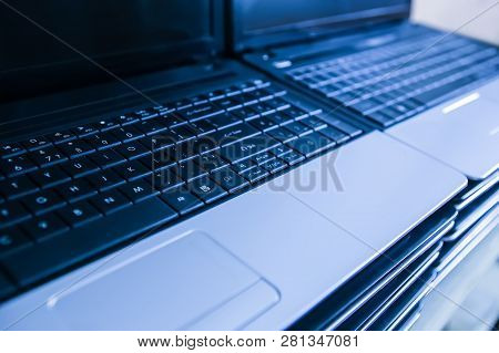 Piles On Laptops With Open Keyboards. Closeup.
