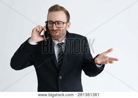 Confused Businessman In Black Jacket Talking On Phone. Young Man In Eyeglasses Using Mobile Phone An