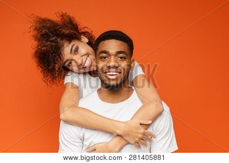 Young African-american Couple In Love Cuddling, Posing On Orange Background, Copy Space