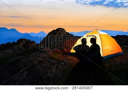 Young Couple Sitting near Illuminated Tent and Looking at Each Other at Beautirul Evening in the Mountains. Adventure and Family Travel Concept.
