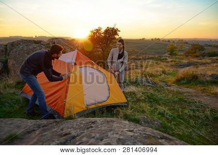 Young Couple Assembling the Tent at Sunset in the Mountains. Adventure and Family Travel Concept.
