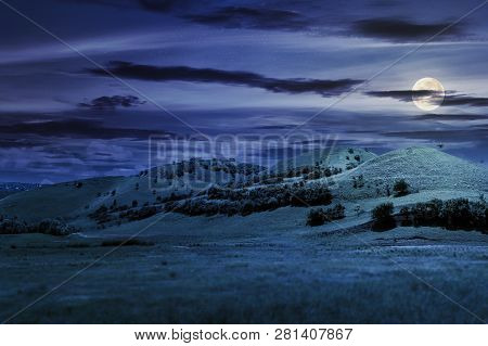Three Hills In Summer Landscape At Night In Full Moon Light. Beautiful Countryside Scenery.  Tilt-sh
