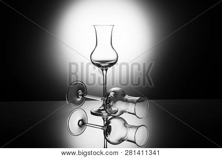 Two classical and elegant glasses for italian grappa backlight, with reflection poster