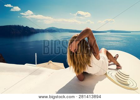 Luxury travel vacation woman looking at view on Santorini island in Greece. Amazing view of sea and Caldera.
