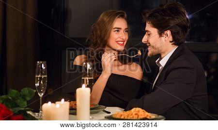 Romantic Couple Having Romantic Dinner In Restaurant, Feeding Each Other.