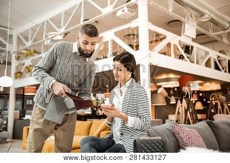 Uncertain Bearded Man Showing Velvet Material To His Wife