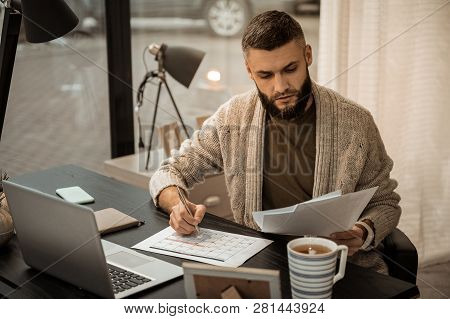 Confused Self-employed Bearded Man Flipping Through Papers