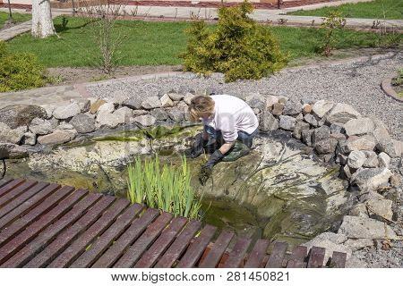 Woman Cleans The Garden Pond. Seasonal Work On The Care Of The Diy Fish Pond