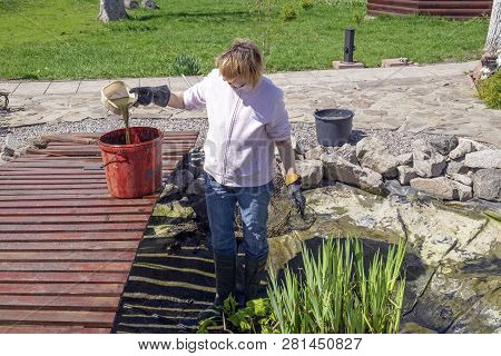 Woman Cleans The Garden Pond. Seasonal Work On The Care Of The Diy Fish Pond Near House