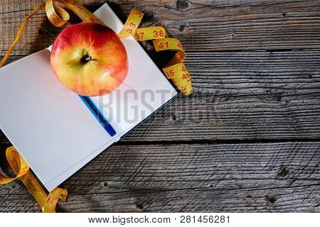 Planning Of A Diet. A Notebook C An Inscription - The Diet, A Measuring Tape, An Apple And Pen