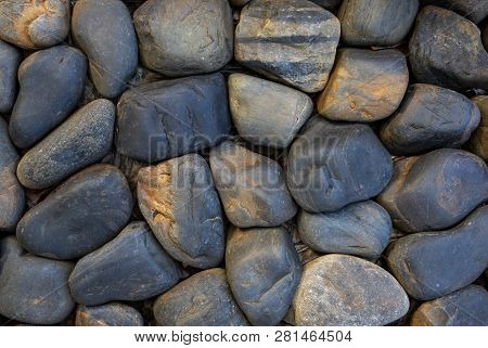 Round Stone Paving. Natural Stone Masonry Top View. Seaside Pebble Photo Texture. Stone Wall Surface